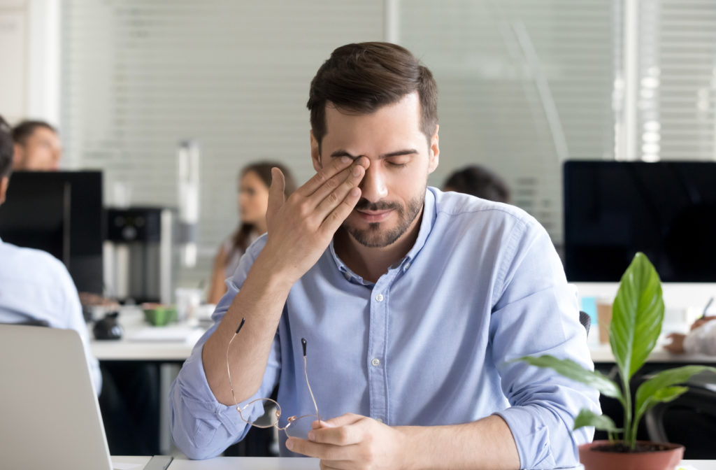 Office worker sitting at desk rubbing his eye while experiencing dry eyes caused by Meibomian Gland Dysfunction