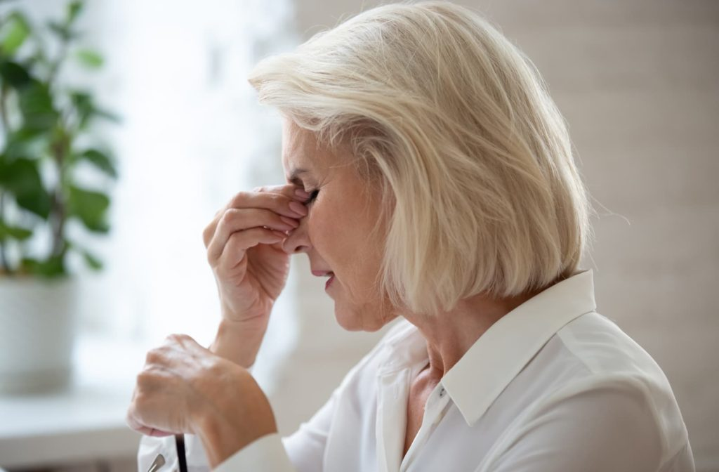 Older woman rubbing her eyes because of dry eye.