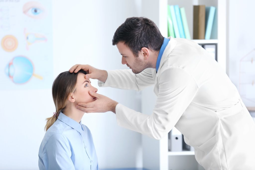 Doctor checking out eyes of patient.