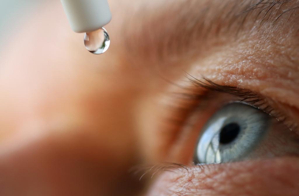 Eye dropper releasing Thealoz Duo into open blue eye