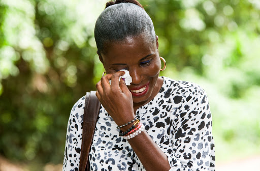 A smiling woman stops to wipe tears from her eye with a tissue while walking outside