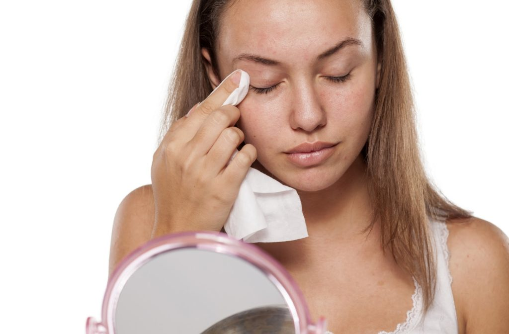 Young woman using face cloth to wipe around eyes while using mirror.